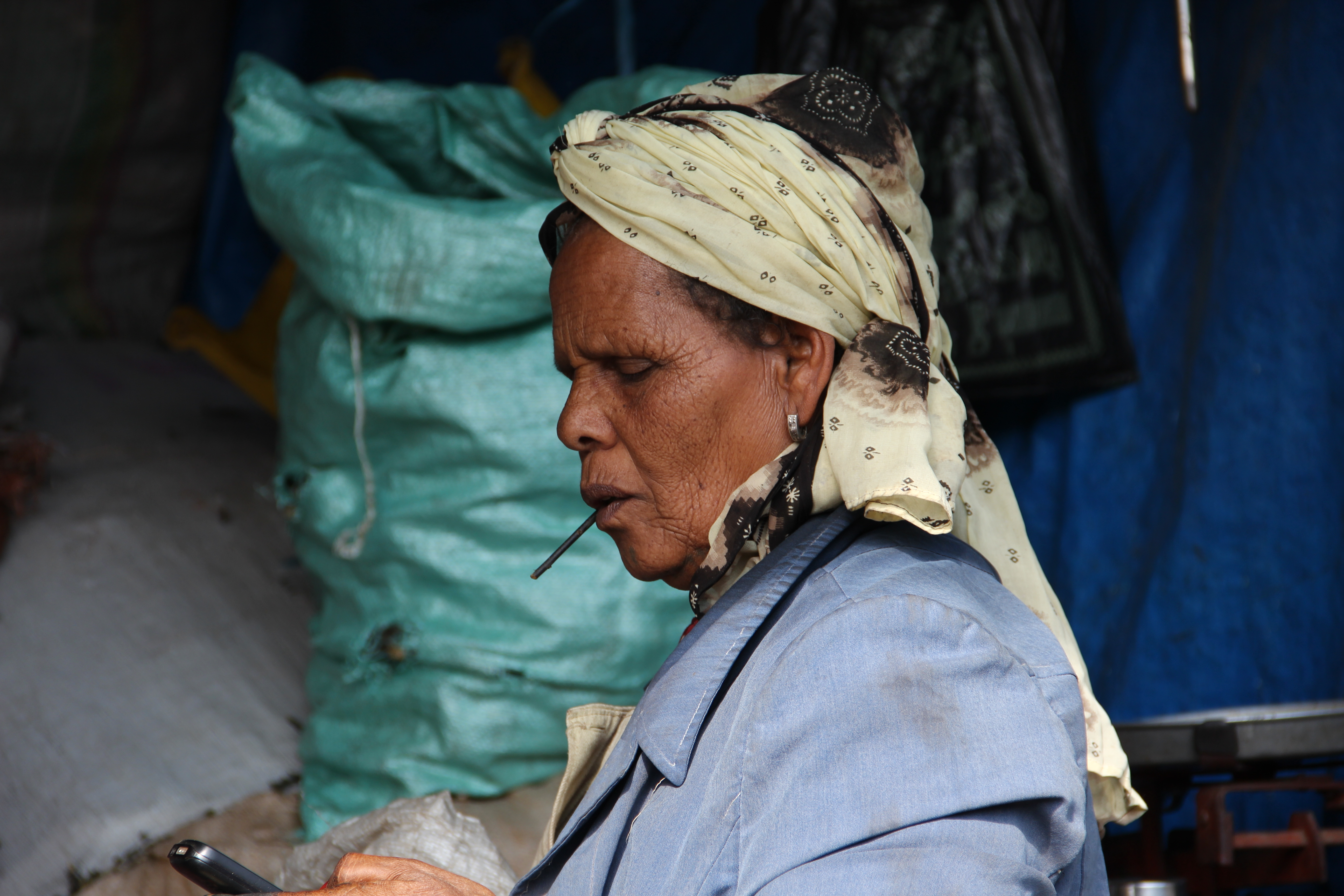 Ethiopian market woman checking her cell phone.